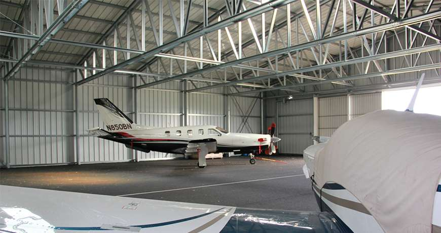 Aircraft Hangar with white and blue jets parked inside a steel structure not insulated metal hall